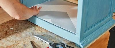 49.Applying_wallpaper_to_cupboard.jpeg
