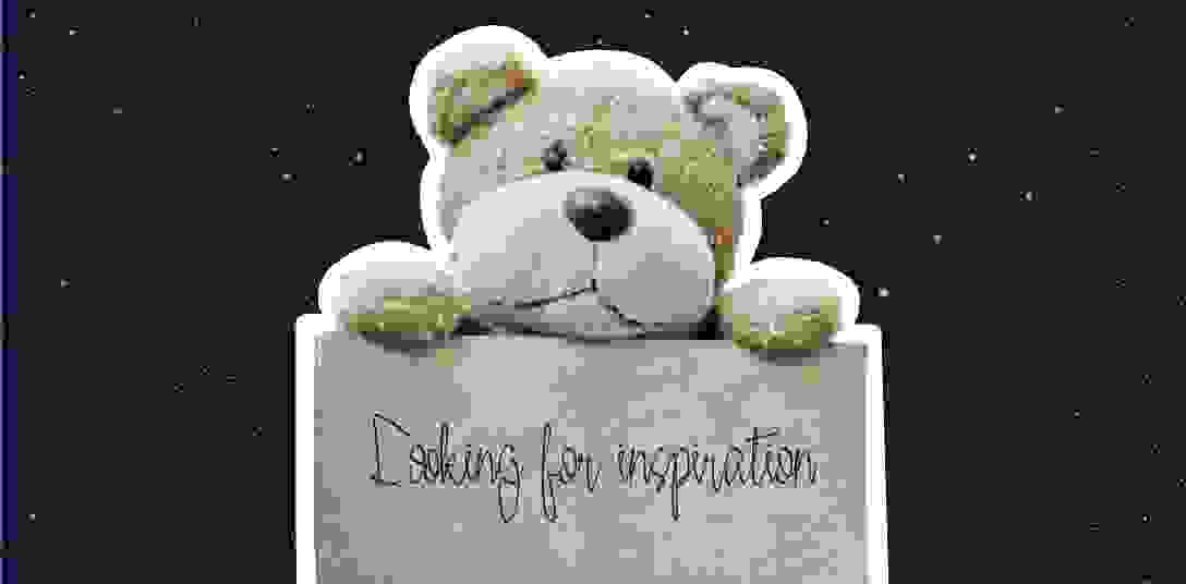 A teddy bear holding a poster that reads looking for inspiration