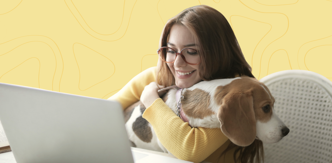 A smiling woman sits in front of her laptop with a dog on her knees and working from home