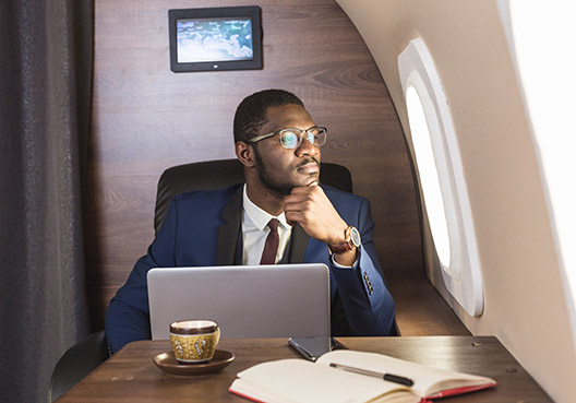 man sitting on a private plane looking out the window with a laptop in front of him