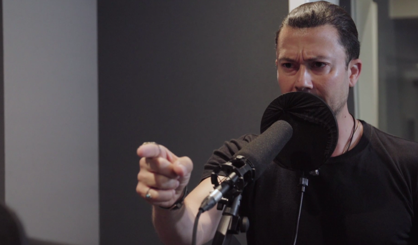 A man records voiceover work at a standing microphone. His expression is stern and his hand points offscreen.