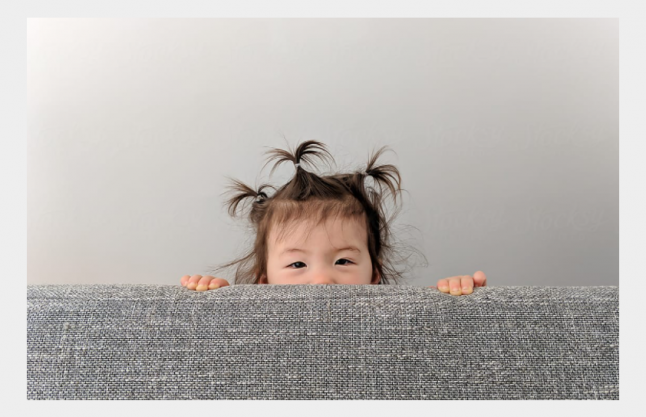 Child behind couch
