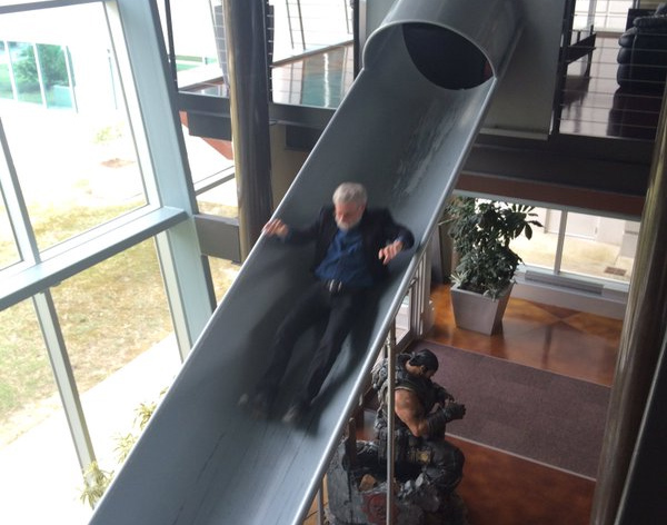 Donald Norman sliding down a slide past a statue of Marcus Fenix