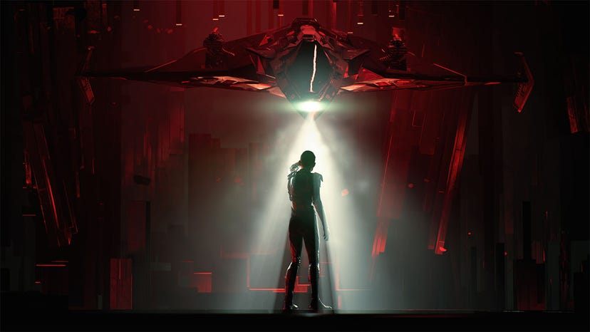 A screenshot of a person standing in a dim, red-lit hangar as a small spaceship shines a cone of light their direction.