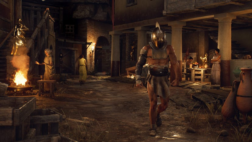 Several people and golden statues in ancient Roman garb populate a dirt road in an ancient Roman city. One woman warms herself by a fire, while another stands near an outdoor dining area. A lightly armored guard walks along the road.