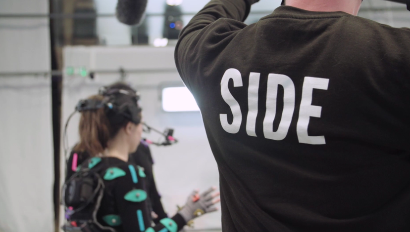 A person in the foreground with the word SIDE printed on their back holds a boom mic toward a woman in a motion capture suit.