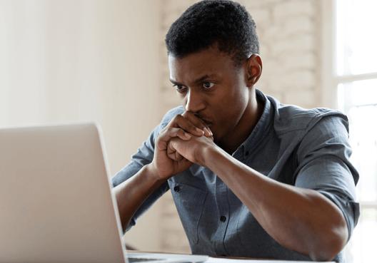 A man sitting worriedly at his desktop looking at his laptop